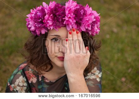Beautiful curvy girl with a flower crown covering her eye in the landscape