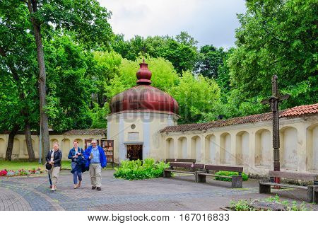 VILNIUS LITHUANIA - JULY 10 2015: Unidentified tourists are going from chapel of Church of Holy Apostles Peter and Paul Vilnius Lithuania