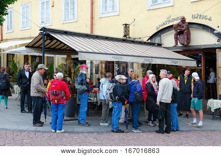 VILNIUS LITHUANIA - JULY 10 2015: Group of tourists are near small cafe at beginning of narrow street Stikliu in Old Town Vilnius Lithuania