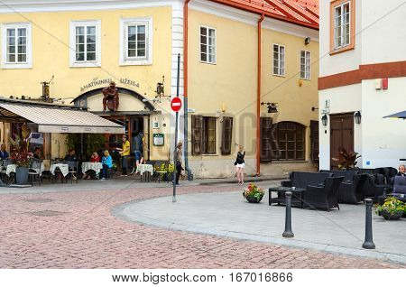 VILNIUS LITHUANIA - JULY 10 2015: Unidentified people are relaxing in small cafe at beginning of narrow street Stikliu in Old Town Vilnius Lithuania