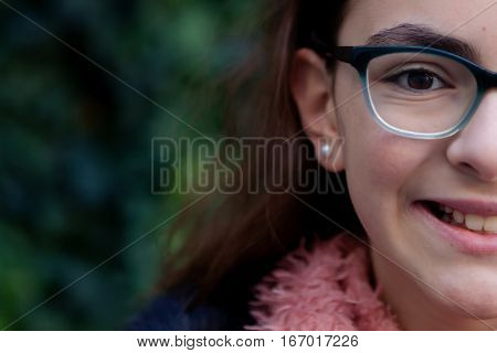 Smiling girl with 12 years old in the garden at winter
