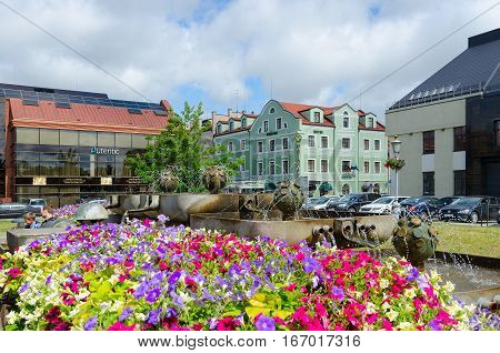 KLAIPEDA LITHUANIA - JULY 11 2015: Unidentified people are relaxing at fountain in front of Salon-shop of amber