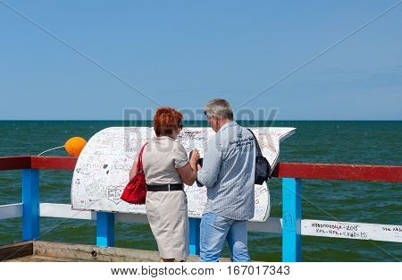 PALANGA LITHUANIA - JULY 12 2015: Unidentified tourists leave inscriptions on special board at famous pier in popular resort town of Palanga Lithuania