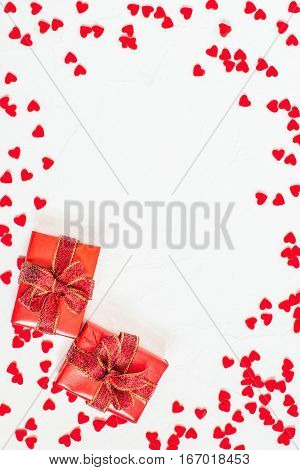 Elegant festive background with decorations in form of heart and gift box with bow on white textured surface with space for text. The mood of tenderness and love. Symbols of Valentines Day. Vertical