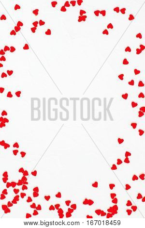 Elegant festive background with decorations in the form of heart on white textured surface with space for text. The mood of tenderness and love. Symbols of Valentines Day. Vertical