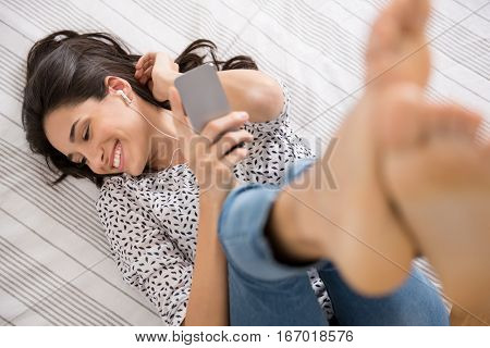 Young woman listening to music with earphones lying down on her bed. Smiling carefree woman lying on bed and listening to music. High angle view of happy girl relaxing her mind and feel the sound.