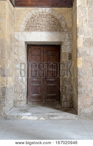 Wooden aged vaulted ornate door and stone wall at Qalawun Complex Medieval Cairo Egypt