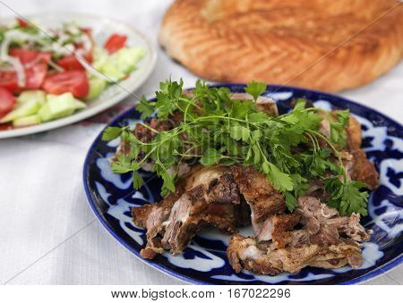 Traditional Uzbek grilled lamb meat with herbs and lavash