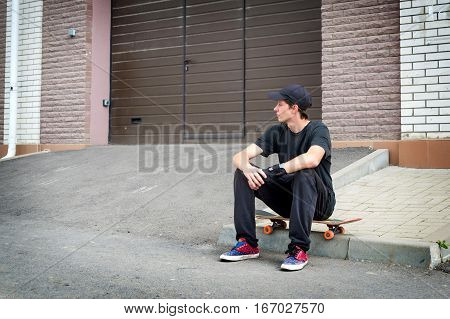 Teenage skateboarder sitting on skateboard with hand protection