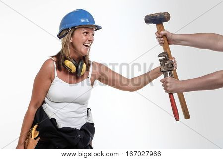 Smiling female constructionworker grabs the tools of her trade