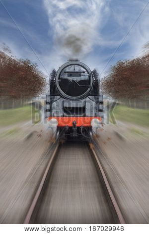 Vintage steam engine hurtles towards the camera as Autumn leaves fly