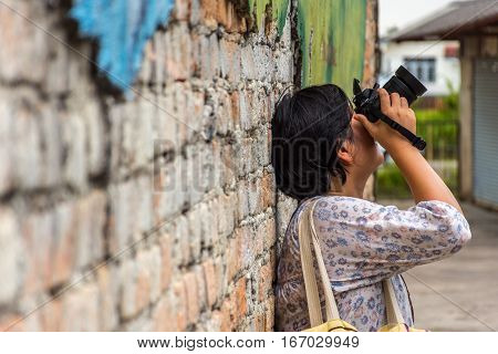 Asia Woman With Camera Against A Brick Wall