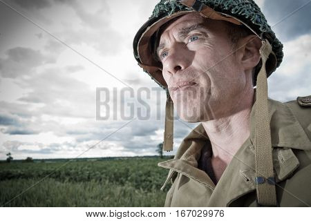 World War 2 era American General Infantry soldier marches through the fields of Normandy, France (re-enactment)