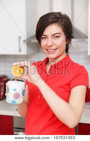 Brunette preparing tea with lemon in kitchen