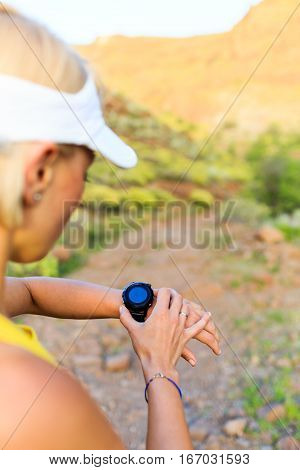 Woman runner checking the elevation on sports watch smartwatch with altimeter app in summer mountains. Young girl training and running on mountain trail in the morning.
