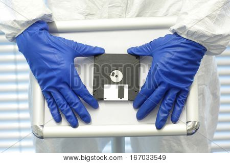 two hands in blue gloves presenting solution - program on old school diskette