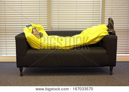 professional in protective clothing, mask and gloves lying and relaxing on the couch at home in office