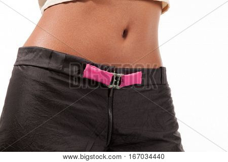 Black girl wearing silk trousers with pink buckle, body part