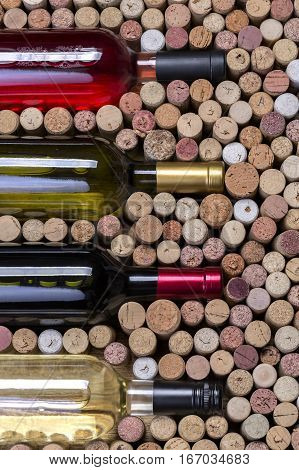 Glass bottle of wine with corks on wooden table background
