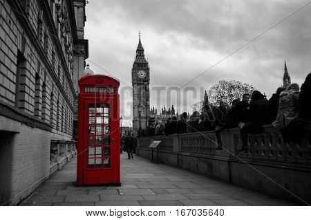 London, UK - November 7, 2015: Selective color photo of a red telephone box in the city center of London UK with the Big Ben in the background on Remembrance Day.