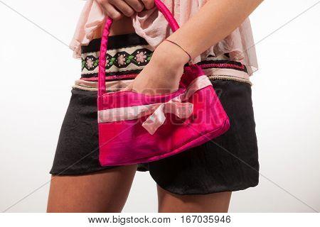 Girl rummages in her handbag latest fashion, portrait in studio