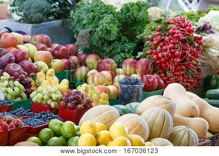 Photo shows close-up view of various fruits and vegetables in the farmers market.