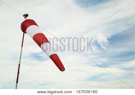 Windsock waving on clouded blue sky background
