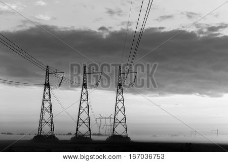 Reliance power lines on background of cloudy sky evening black and white photo