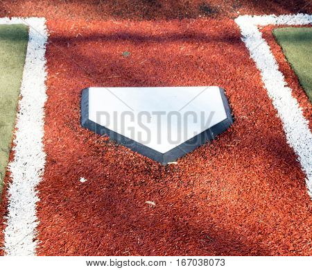 Home plate on a red and green turf baseball field