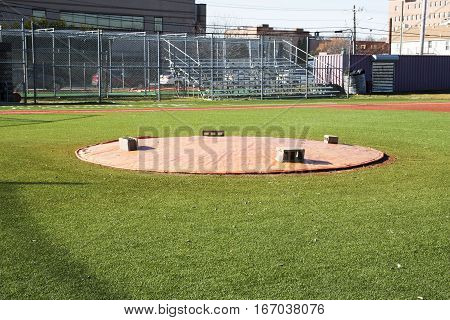 A baseball pitchers mound is covered with a tarp keeping it in good shape for game day