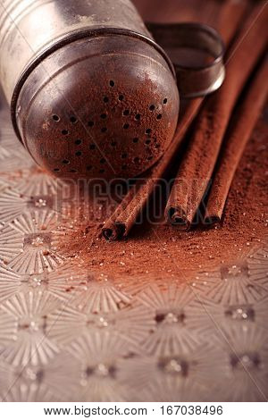 vintage sifter with cocoa powder and cinnamon sticks