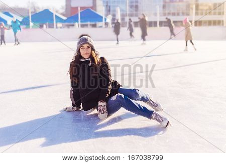 Ice Skating Woman Sitting On The Ice Smiling.