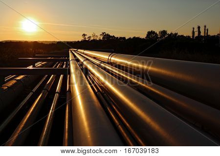 golden steel pipeline system in refinery during sunset