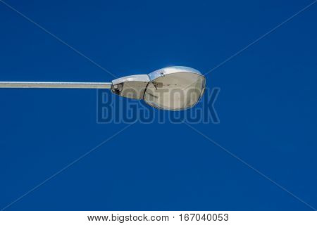 close up street lamp with blue sky background.