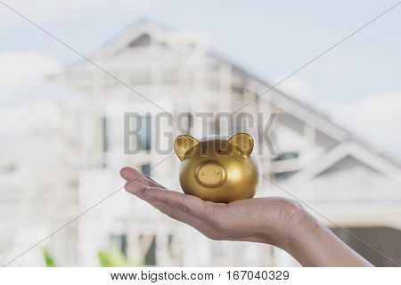 gold piggy bank on hand women with house construction background