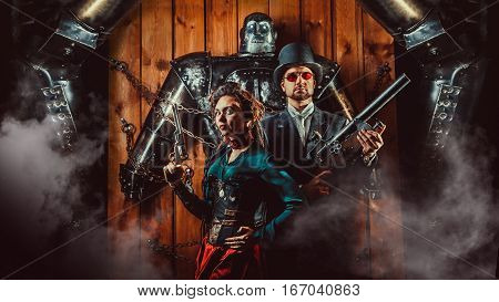 Beautiful Couple With The Guns And Big Tied Robot On The Background.