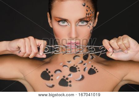 young woman with animal patterns and collar on dark background