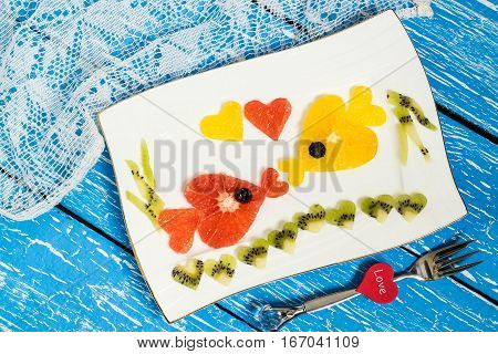 Creative idea of food decoration for Valentines Day. Fruit salad with citrus. Two kissing goldfish composed of hearts cut from grapefruit orange kiwi. Symbols of Valentines Day in the design
