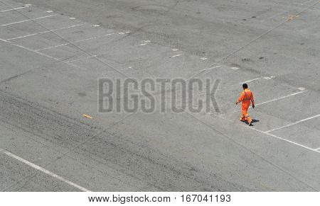 Unrecognized Male Worker wearing a red suit walking on the road