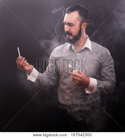 Handsome Businessman With E-cigarette And Tobacco Cigarette Wearing Suit On Black Background