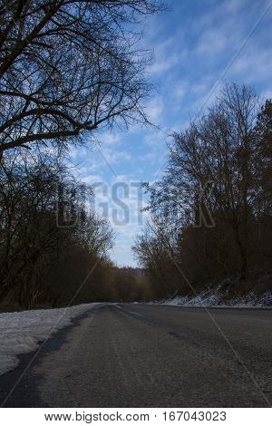 lonely winter road with blue sky full of clouds