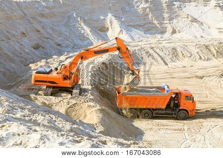 Excavator loading dumper truck with sand at a sand quarry
