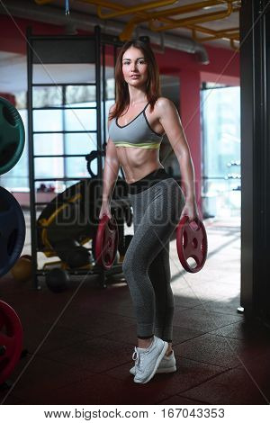 Full length shot of young woman in sportswear in the gym and looking at kettle bell on floor. Fitness female getting ready for intense crossfit workout. poster