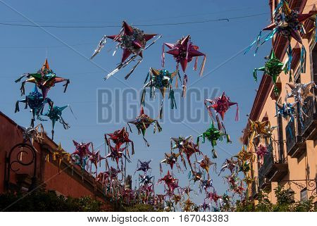 Countless pinatas against a blue sky over a street in a Mexican town