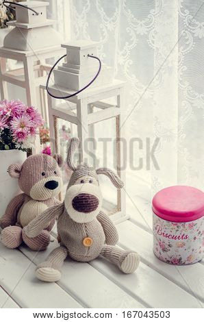 Provence style interior - warm and cozy window seat with Teddy Bears and flowers. Light home decoration in pink and purple tones. Retro living room.