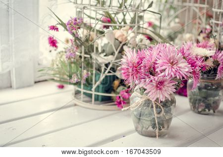 Provence style interior-beautiful pink and purple bouquets in vase and cages over window. Light home decoration with flowers asters. Retro living room. Vintage holiday floral concept. Copy space.