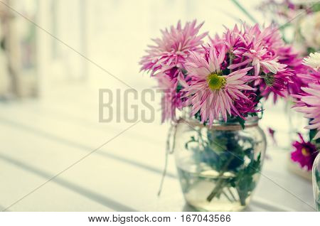 Beautiful pink and purple bouquet in glass vase over window. Light home decoration with flowers asters. Provence style interior retro living room. Vintage holiday floral concept. Copy space.