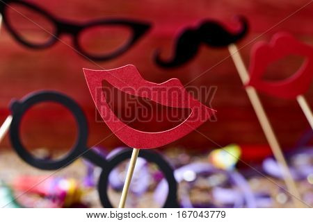 some different mouths, eyeglasses and mustaches attached to sticks, to use as handles, against a red background and a wooden surface full of confetti