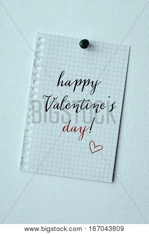 closeup of a piece of paper, with the text happy valentines day written in it, pinned in a wall with a push pin, with a blue tone
