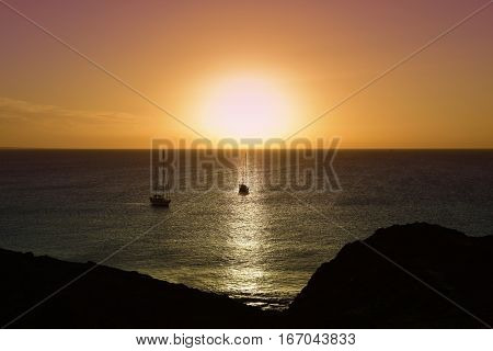 a view of some sailboats, the sun and the Atlantic ocean at dusk, from the Playa Mujeres beach in Playa Blanca, Lanzarote, in the Canary Islands, Spain